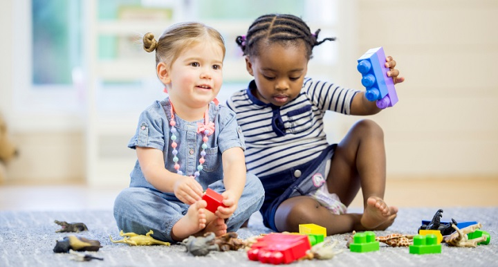 A multi-ethnic group of toddlers are sitting on the floor playing with toy animals happily.